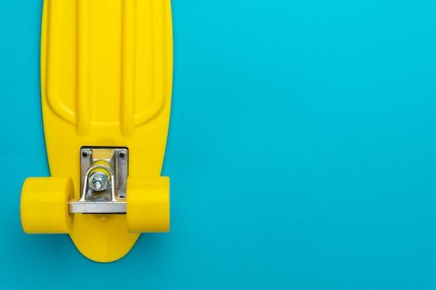Photo plate minimaliste de skateboard cruiser sur fond bleu turquoise