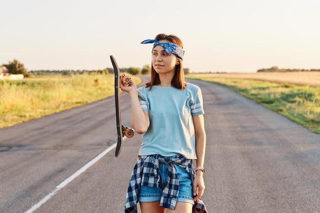 Photo en plein air d'une belle femme aux cheveux noirs portant un bandeau, un t-shirt et un short, tenant un longboard dans les mains et détournant les yeux avec une expression réfléchie.