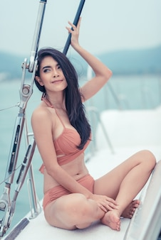 Photo de plein air estivale fashion de sexy fille aux cheveux noirs en bikini luxueux reposant sur un yacht à la mer