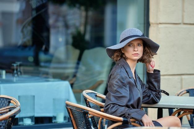 Photo en plein air d'une femme élégante portant un manteau à l'ancienne, ayant une pause dans un café en plein air de la rue