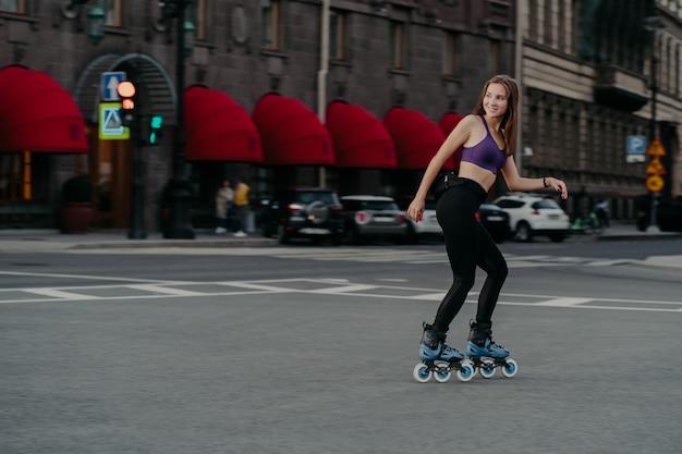 Photo en plein air d'une femme mince active vêtue d'un haut court et de leggings patins à roues alignées à travers la ville profite d'un excellent entraînement physique brûle des calories obtient de l'énergie soulage le stress apprend de nouvelles compétences