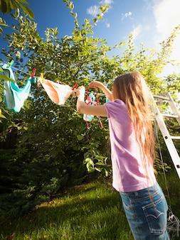 Photo en plein air d'une fille faisant la lessive et séchant des vêtements au jardin