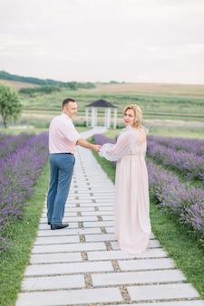 Photo en plein air d'un heureux couple d'âge mûr romantique amoureux marchant sur un sentier à travers un champ de lavande en fleurs, se tenant la main et profitant de moments ensemble