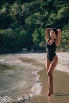 Photo en plein air de mode de belle femme sensuelle avec de longs cheveux noirs en maillot de bain noir élégant relaxant sur la plage