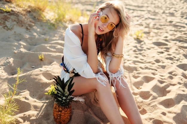 Photo en plein air de mode de vie de rire jolie femme à l'ananas juteux reposant sur la plage ensoleillée. tenue d'été tendance