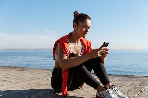 Photo en plein air d'une sportive séduisante faisant une pause près de la mer, assise sur une jetée en bois et utilisant la mobi...
