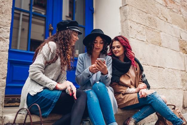 Photo en plein air de trois jeunes femmes regardant un smartphone dans la rue. filles parlant et s'amusant à l'extérieur