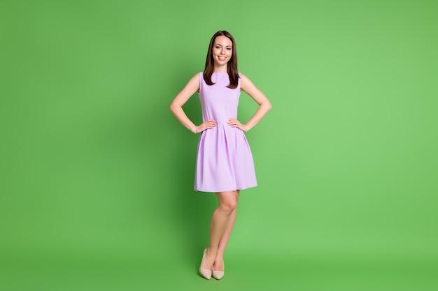 Photo pleine grandeur de belle belle fille optimiste dame mains taille chaussures beiges jambes minces look caméra annonce modèle école rayonnant sourire porter robe violette isolé fond de couleur vert pastel