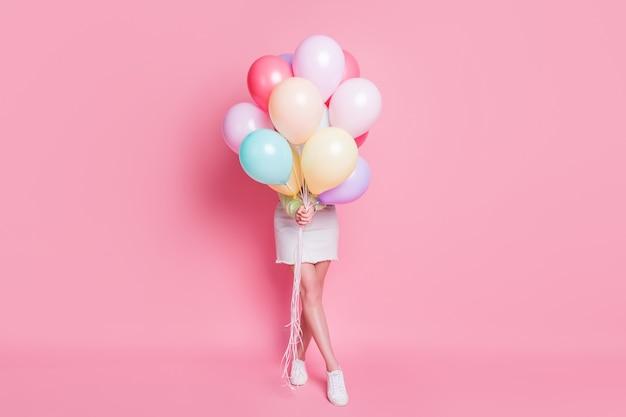 Photo pleine grandeur d'une dame drôle venue fête d'anniversaire tenir de nombreux ballons à air cachant le visage visite surprise porter des vêtements décontractés verts pull-over jeans jupe chaussures isolés fond de couleur pastel rose