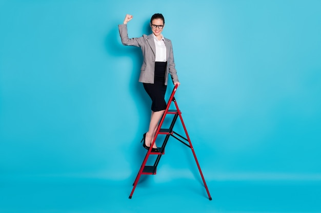 Photo pleine grandeur dame patron stand carrière échelle montrer triceps porter jupe blazer isolé fond de couleur bleu