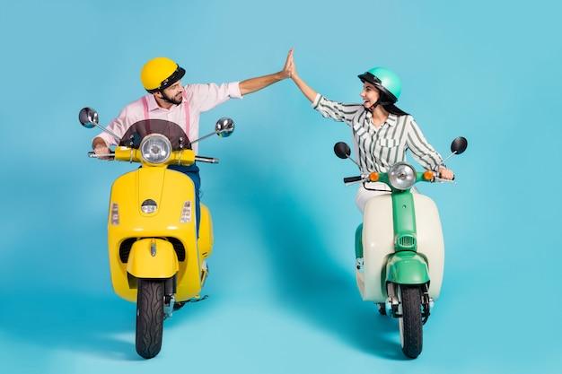 Photo pleine grandeur de drôle deux personnes dame guy conduire rétro cyclomoteur une équipe de voyageurs bonne humeur clap bras vêtements de cérémonie casquettes de protection mur de couleur bleu isolé