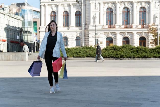 Photo pleine grandeur de femmes touristiques avec des sacs en papier sur un beau fond de bâtiment.