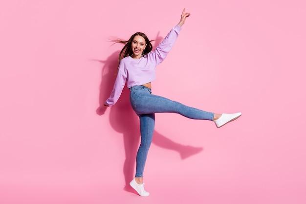 Photo pleine grandeur d'une fille candide énergique profitez des vacances de week-end de réjouissance lever la main de la jambe porter des vêtements à la mode coiffure air vent voler isolé sur fond de couleur pastel