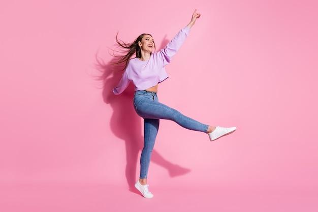 Photo pleine grandeur d'une fille excitée et candide profitez du temps libre pour regarder la surface de la copie soulever la jambe de la main porter des chaussures à la mouche à la mode et à la mode isolées sur fond de couleur pastel