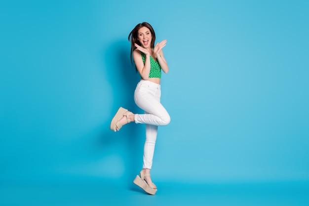 Photo pleine grandeur d'une fille joyeuse positive étonnée qui saute la remise de la saison impressionnée porte des vêtements de bonne apparence, des chaussures isolées sur fond de couleur bleu
