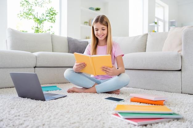 Photo pleine grandeur d'une fille positive étudier à distance lire un livre leçon en ligne tâche scolaire préparer la tâche à la maison s'asseoir tapis jambes croisées ed dans la maison le week-end à l'intérieur