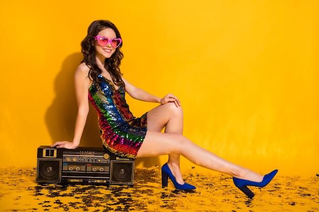 Photo pleine grandeur de fille positive s'asseoir boom box confettis étage porter des lunettes de soleil en forme de coeur jupe stilettos isolé sur fond de couleur brillant brillant