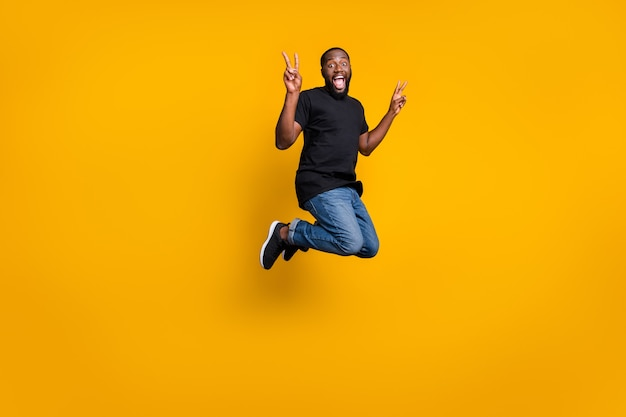 Photo pleine grandeur de funky fou afro-américain brunette cheveux guy saut amusant printemps week-ends vacances faire v-signes porter des baskets tenues élégantes isolé sur mur de couleur brillance