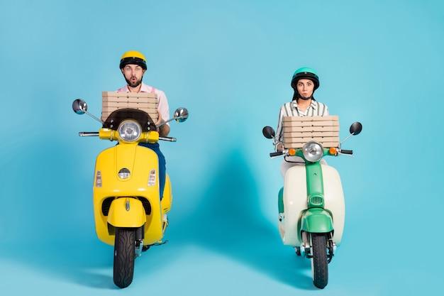 Photo pleine grandeur de funky lady guy conduire deux cyclomoteurs rétro transporter des boîtes à pizza courriers entreprise familiale livraison de restauration rapide tenue de soirée casque de protection mur de couleur bleu