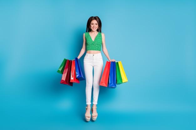 Photo pleine grandeur de jolie fille sauter tenir de nombreux sacs profiter du centre commercial porter des vêtements de centre commercial en pointillé vert débardeur débardeur pantalon blanc pantalon sandales isolées sur fond de couleur bleu