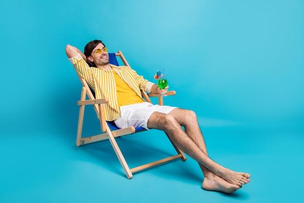 Photo pleine grandeur mec positif profiter du repos se détendre station balnéaire exotique bain de soleil tenir cocktail en verre s'asseoir transat porter des shorts chemise rayée jaune blanc pieds nus isolé fond de couleur bleu