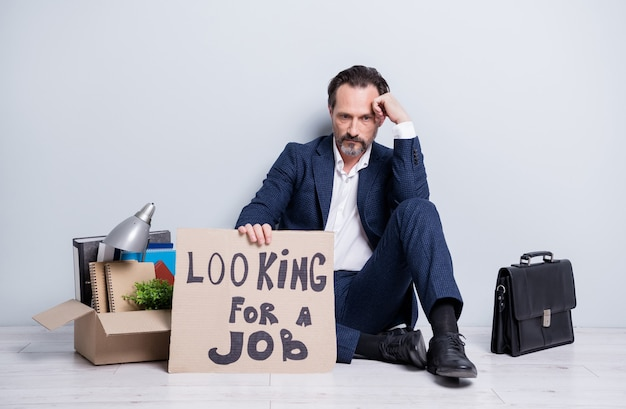 Photo pleine grandeur de perdant congédié travailleur homme d'âge mûr homme d'affaires homme sans emploi tenir une pancarte besoin de recherche travail s'asseoir sol mallette affaires boîte trucs porter costume chaussures isolé fond gris