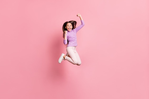 Photo pleine grandeur d'une petite fille extatique qui saute les poings et porte un pull violet isolé sur fond de couleur pastel