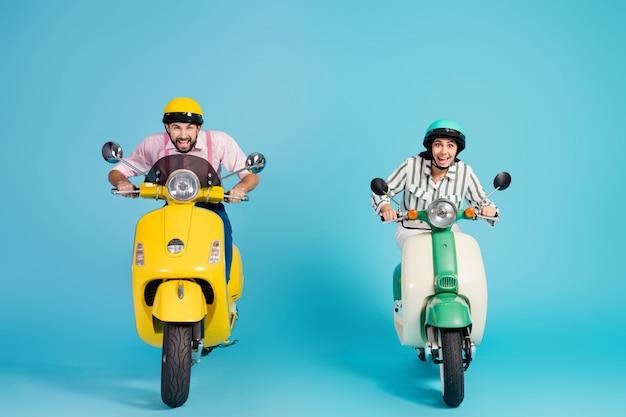 Photo pleine grandeur de se précipiter drôle deux personnes dame guy conduire rétro cyclomoteur grande vitesse voyageurs moyen facile bonne humeur vêtements de cérémonie vêtements casquettes de protection mur de couleur bleu isolé