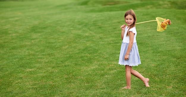 Photo pleine longueur d'une adorable petite fille regardant la caméra debout avec un filet à papillons attrapant