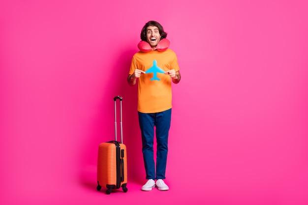 Photo pleine longueur de l'affaire de l'homme montre un avion en papier bouche ouverte porter un coussin de cou t-shirt orange jeans baskets isolé fond de couleur rose