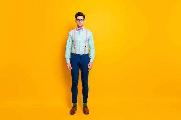 Photo pleine longueur de beaux vêtements cool mec copain se tenir avec confiance ne pas sourire porter spécifications bretelles chemise pantalon noeud papillon chaussures chaussettes isolé fond de couleur jaune vif