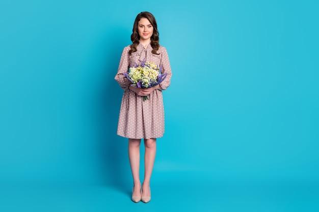 Photo pleine longueur de la belle charmante dame à la coiffure ondulée tenant un grand bouquet surprise de fleurs sauvages présent le 8 mars, la journée des femmes porte des talons aiguilles isolés sur fond bleu