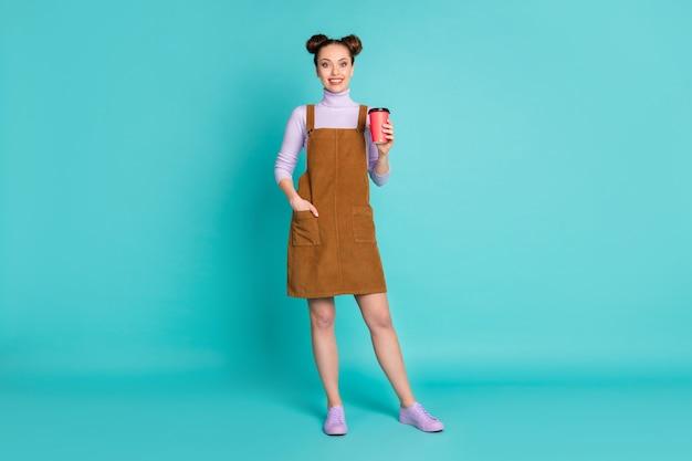 Photo pleine longueur d'une belle deux brioches coiffure dame marche rue repos boisson chaude cacao poche à main porter chaud automne robe de velours marron pull violet baskets isolées fond de couleur turquoise