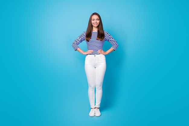 Photo pleine longueur de belle jeune fille en bonne santé fit figure mains hanches côtés guide paquebot de croisière rencontrer des passagers porter chemise rayée pantalon blanc baskets isolé fond de couleur bleu