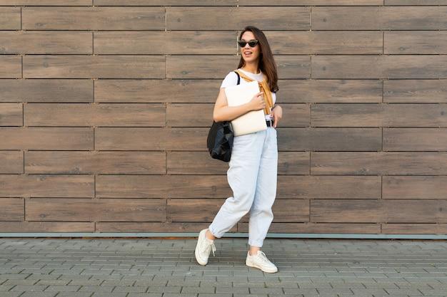 Photo pleine longueur d'une charmante jeune femme brune beautify allant dans la rue près du mur marron
