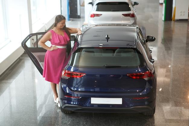 Photo pleine longueur d'une cliente examinant l'intérieur d'une voiture à vendre chez un concessionnaire