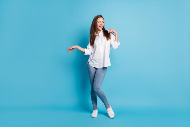 Photo pleine longueur de dame drôle bonne humeur danse look côté porter chemise blanche jeans baskets isolé fond de couleur bleu