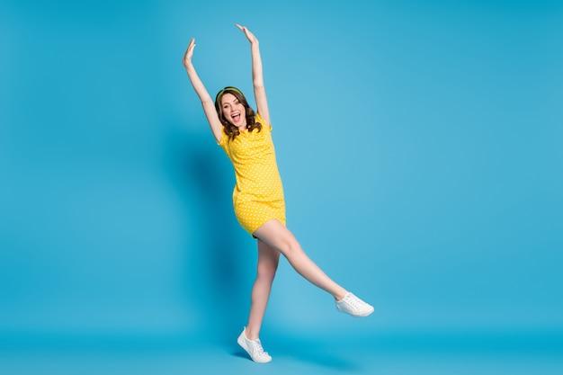 Photo pleine longueur d'une dame excitée qui lève les mains sur une jupe à pois isolée sur fond de couleur bleu