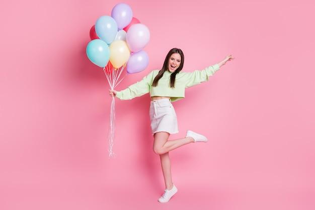 Photo pleine longueur d'une dame séduisante organiser une fête d'anniversaire avec un ami tenir de nombreux ballons à air rencontrer des invités porter un pull vert décontracté en jean jupe chaussures isolées fond de couleur pastel rose