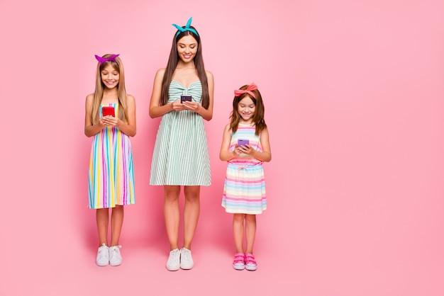 Photo pleine longueur de dames intéressées avec une coupe de cheveux brune blonde ayant des bandeaux utilisent une robe jupe usure gadget isolé sur fond rose