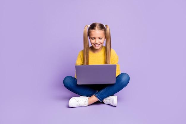 Photo pleine longueur de l'enfant intéressé positif assis les jambes croisées travail plié son ordinateur portable lire les médias sociaux nouvelles portent des vêtements de style décontracté isolé sur mur de couleur violet