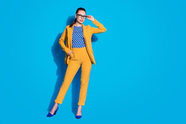 Photo pleine longueur d'une femme d'affaires attrayante qui réussit à tenir des lunettes de lecture de vision à la main porter un costume de blazer jaune chemise chemisier en pointillé isolé fond de couleur bleu vif