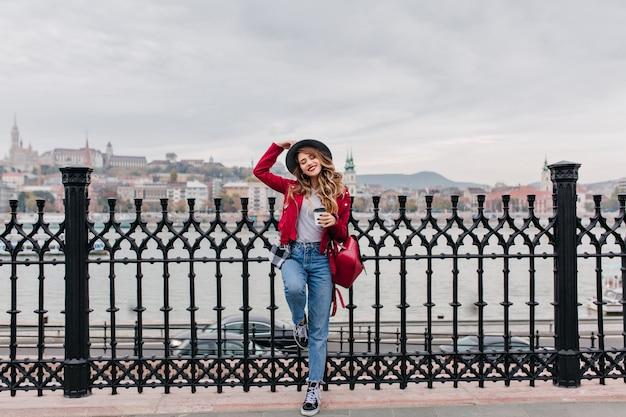 Photo pleine longueur d'une femme confiante au chapeau debout sur une jambe au pont