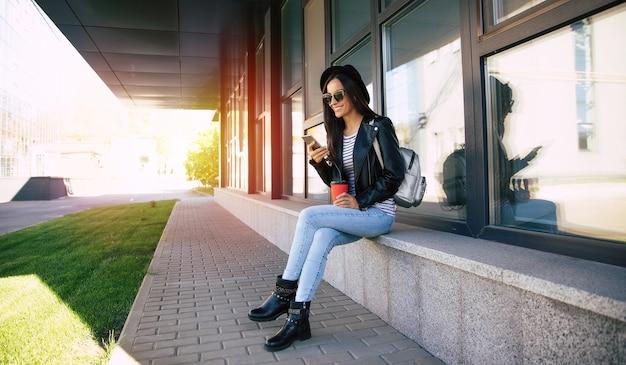 Photo pleine longueur d'une femme élégante portant un chapeau noir et des lunettes de soleil, assise près d'un bâtiment moderne, vérifiant l'alimentation de son smartphone et buvant du café