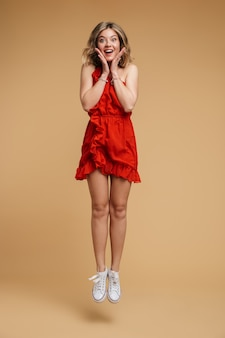 Photo pleine longueur d'une femme européenne excitée de 20 ans vêtue d'une robe rouge souriante et sautant isolée sur un mur beige