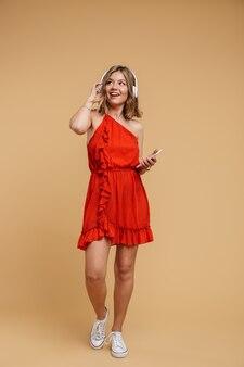 Photo pleine longueur d'une femme européenne portant une robe rouge tenant un téléphone portable et écoutant de la musique avec des écouteurs isolés sur un mur beige