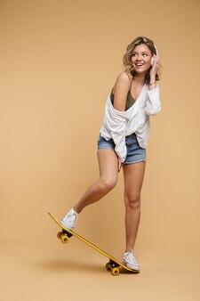 Photo pleine longueur d'une femme européenne positive portant un short en jean avec des écouteurs et une planche à roulettes isolée sur un mur beige