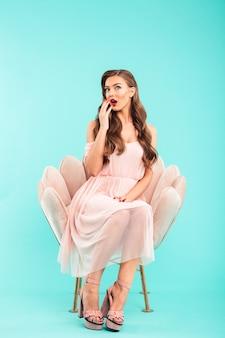 Photo pleine longueur d'une femme excitée de 20 ans en robe rose assis dans un fauteuil moelleux avec les jambes croisées et la bouche ouverte, isolée sur un mur bleu