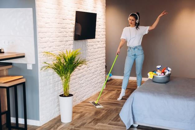 Photo pleine longueur d'une femme joyeuse heureuse lave le sol dans la chambre avec une vadrouille en s'amusant