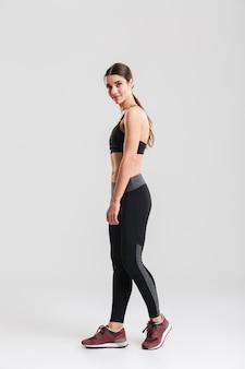 Photo pleine longueur de femme mince sportive portant un survêtement et regardant, isolé sur mur gris
